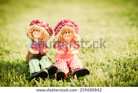Two Lovely doll sitting on green grass background in a vintage retro style, with the sunrise, for the day of love, - stock photo