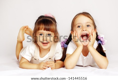 Two lovely little girls playing on the floor - stock photo