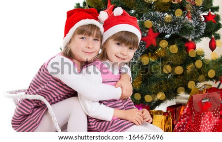 Two lovely sisters hugging in sledge under Christmas tree