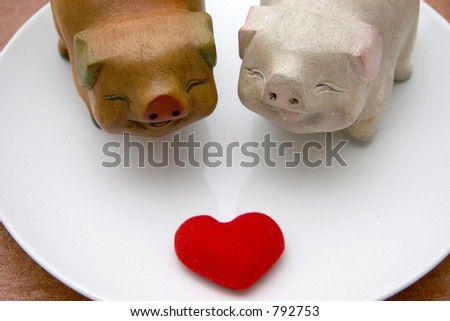 Two lovely smiling wooden pigs facing a soft heart for Valentines on a white platform - stock photo