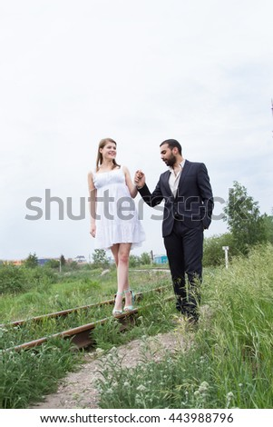 Two lovers are walking on railroad tracks