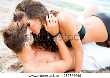 Two lovers at beach holding each other with lens flare and warm image tone,pretty girl cuddling with boyfriend on sand,shallow depth of field,loving happy couple on tropical beach,passion kiss - stock photo