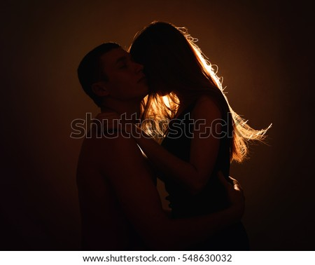 Two lovers. Kissing man and woman. Couple in contrast back light.