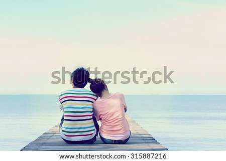 Two lovers sitting on the bridge at the sea. - stock photo