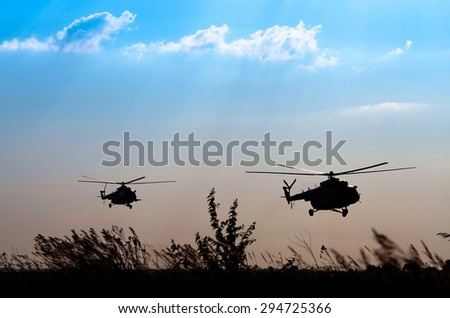 two low-flying transport helicopters