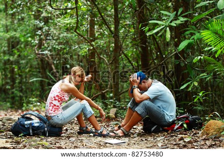 Two mad young people loosing way and sitting in the forest on the backpack - stock photo