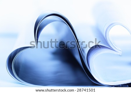 Two magazines folded to heart shape on table - stock photo