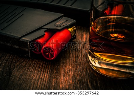 Two magazines with red cartridges 12 gauge and glass of whiskey on the wooden table. Close up view, image vignetting and the orange-blue toning - stock photo