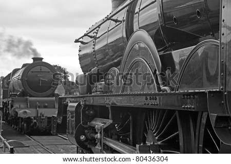 Two mainline steam trains facing each other across an old style turntable. Old steam. - stock photo