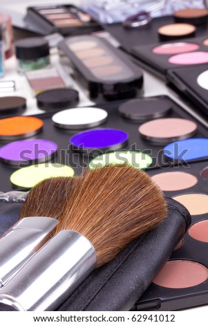 Two make-up brushes on eyeshadows palettes, closed-up