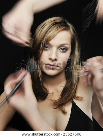 Two Makeup artist  help girl getting her makeup - stock photo