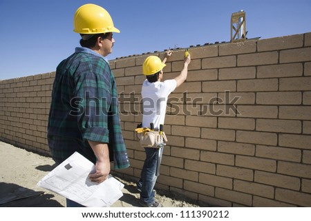 Two male architects inspecting brick wall at construction site - stock photo