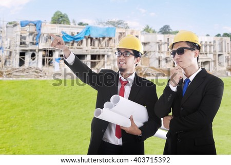 Two male contractor look at the residential construction and discussing together - stock photo