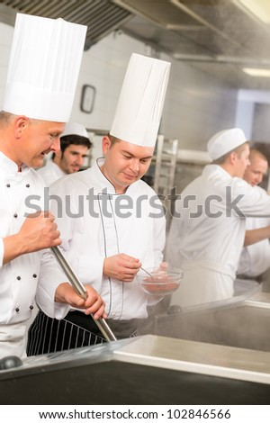 Two male cooks working in professional industrial kitchen prepare food - stock photo