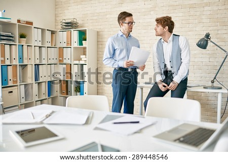Two male employees discussing plans in office - stock photo