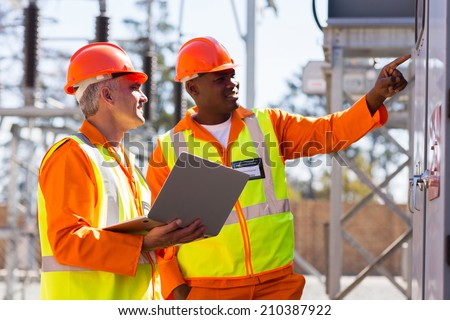 two male engineers working in electrical substation - stock photo