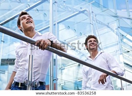 Two Male executive standing and looking up - stock photo