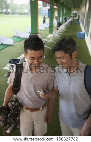 Two male friends smiling and getting ready to leave the golf course - stock photo