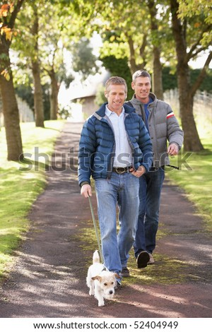 Two Male Friends Walking Dog Outdoors In Autumn Park Together - stock photo