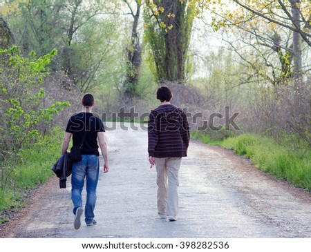 Two male friends walking in the nature on sunny spring day. - stock photo