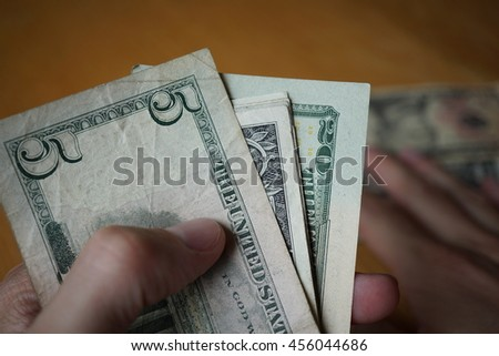 Two male hands holding a set of paper banknotes (American Dollars, USD) and giving the money on the wooden table as a symbol of ongoing money transfer (payment, bribery or gift)