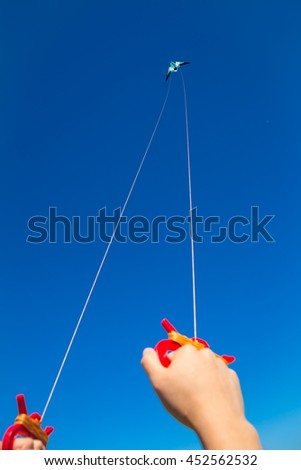 Two male hands holding kite strings with a kite  in sky at distance - stock photo