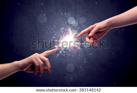 Two male hands reaching towards each other, almost touching with fingers, lighting spark in galaxy background concept - stock photo