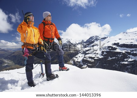 Two male mountain climbers on snowy peak against sky with one using walkie talkie - stock photo