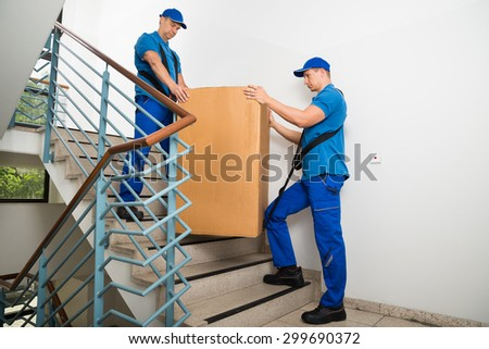 Two Male Movers In Uniform Standing With Box On Staircase - stock photo