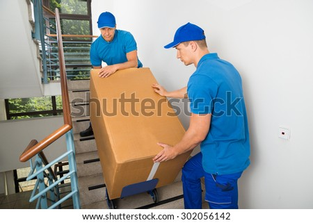 Two Male Movers Walking Downward With Box On Staircase - stock photo