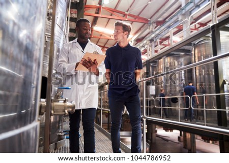Two male staff members make an inspection at a wine factory