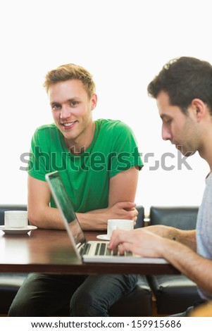Two male students using laptop while having coffee at  the coffee shop - stock photo