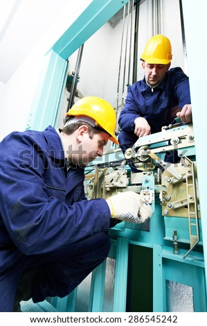 two male technician machinist worker at work adjusting elevator mechanism of lift with spanner - stock photo