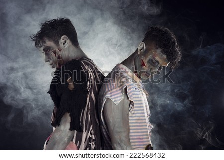 Two male zombies back to back on black smoky background, looking down and away - stock photo