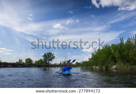 Two man are kayaking on a river in beautiful nature - stock photo