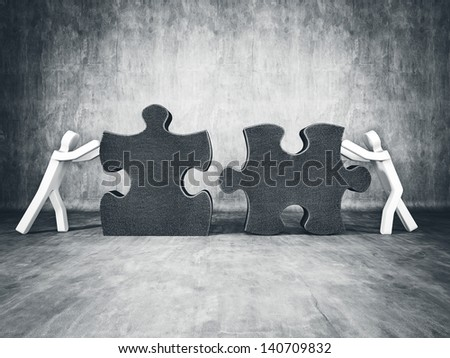 two man building puzzle on concrete background - stock photo