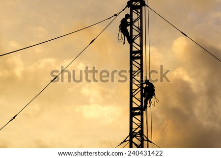 Two Man in silhouette working on communication or electricity tower - stock photo