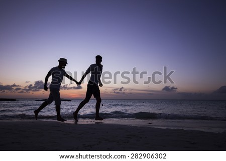 Two man running on the beach holding hands, at sunset. Isla Mujeres, Mexico. - stock photo