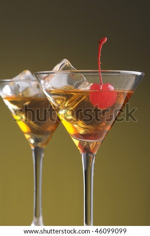 Two Manhattan Cocktails in Martini Glasses on a warm background. Vertical format shot from a low angle. - stock photo