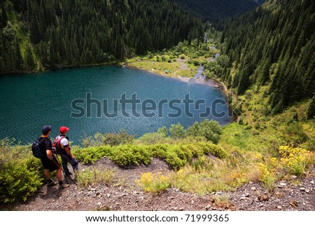 Two mans admiring the beauty of Kolsai lake, Kazakhstan - stock photo