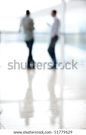 Two mans silhouette in hall of office building - stock photo
