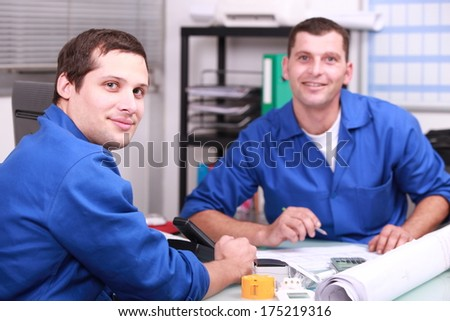 Two manual worker in the office checking stock levels - stock photo