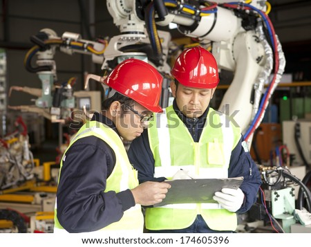 Two manufacture worker discussing in factory - stock photo