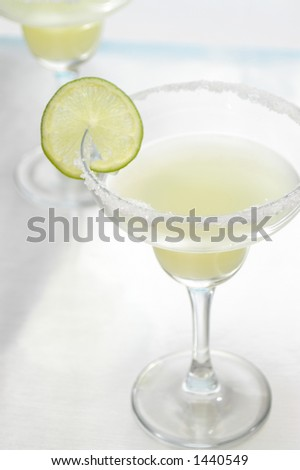 Two margaritas, focus on salty rim. - stock photo