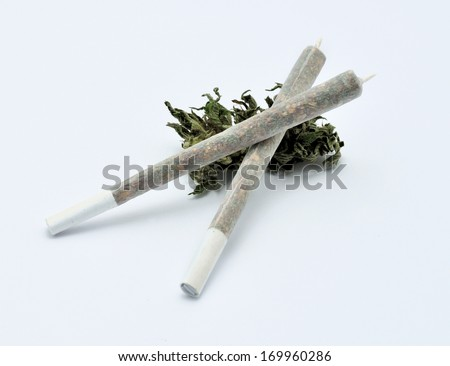 Two marijuana joints placed on white background - stock photo