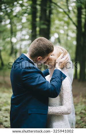 Two married people kissing in the forest