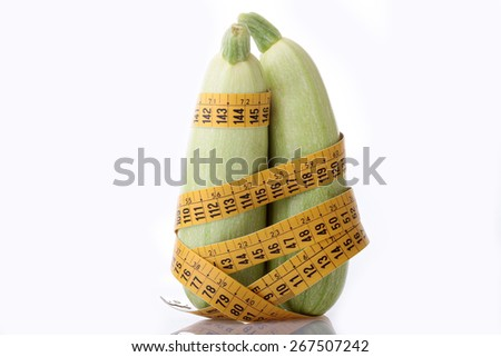 Two marrow zucchini zucchini and measuring tape on white background - stock photo