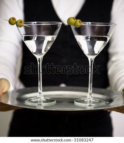 Two martini glasses on round silver tray - stock photo