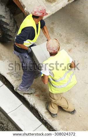 two mason construction workers carrying a tile to repair sidewalks in the street city - stock photo