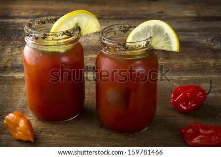 Two mason jar Bloody Marys or Caesars with lemon and lime on wood background